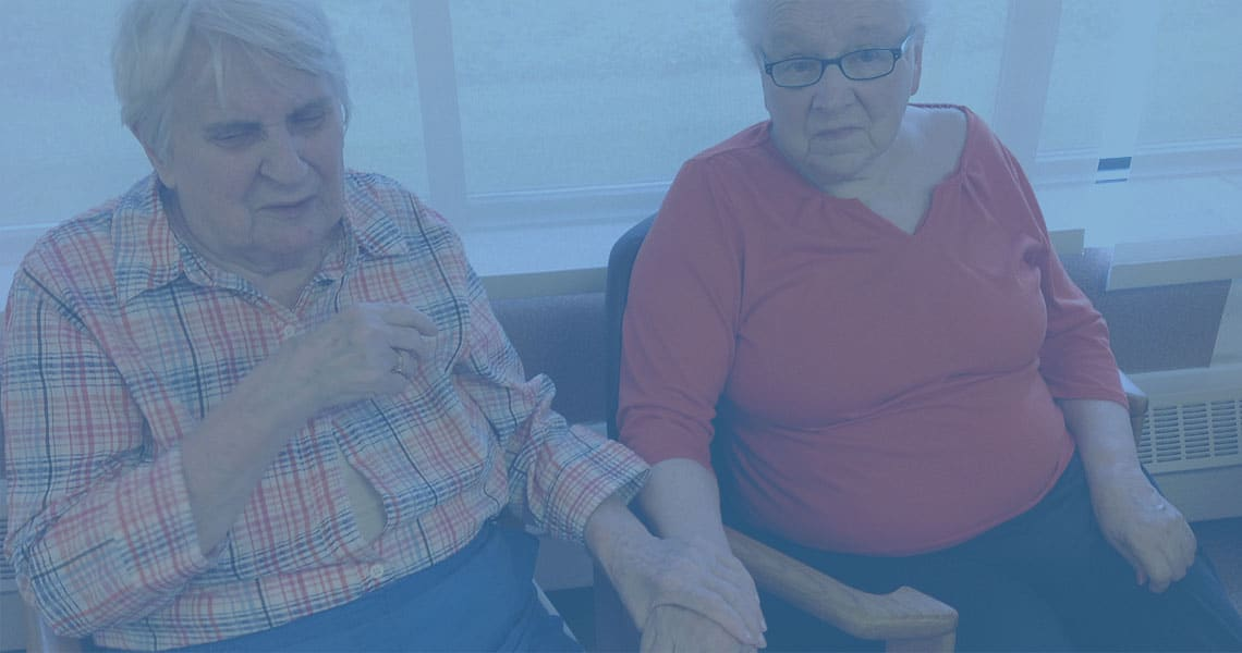 Photo of two Marianhill residents sitting together, holding hands