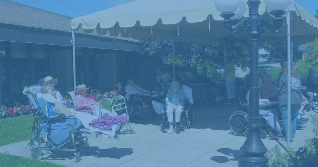 Photo of Marianhill residents sitting under a canopy in the garden