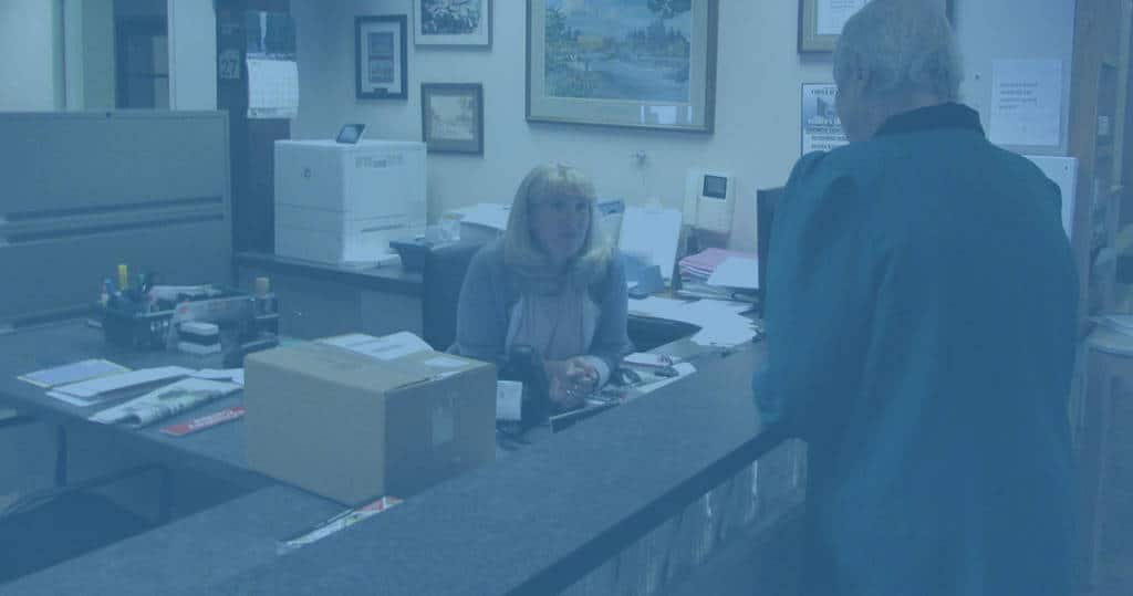 Photo of staff and resident at Marianhill reception desk