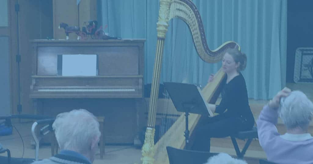 Photo of woman playing a harp in Marianhill auditorium
