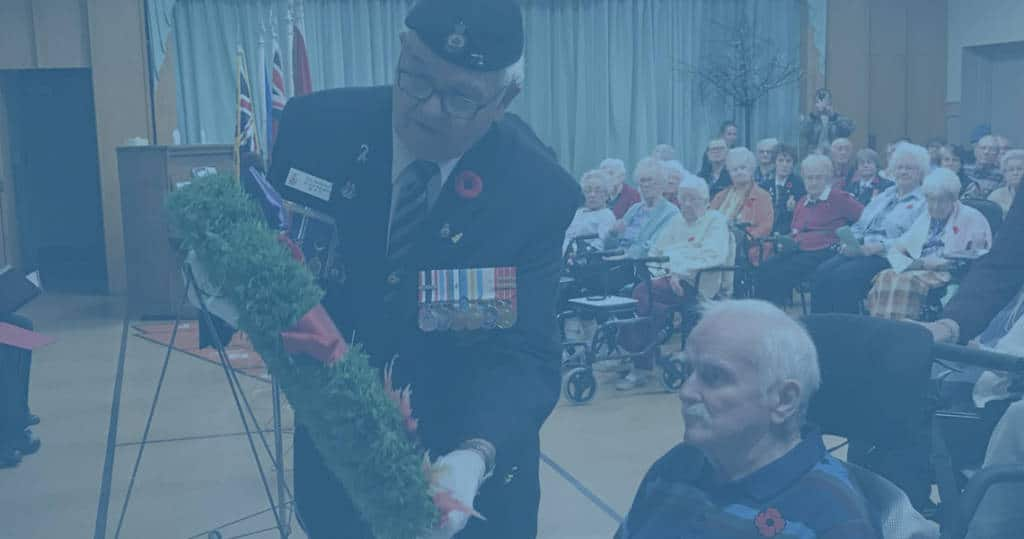 Photo of veteran laying wreath with help of man in wheelchair